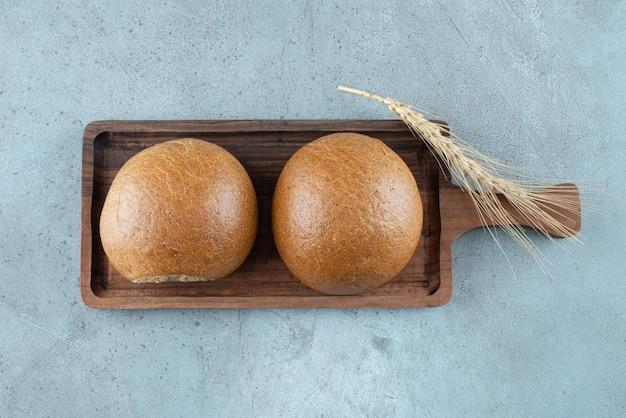Deux petits pains frais sur planche de bois avec du blé.