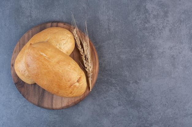 Deux petits pains et une seule tige de blé sur une planche de bois sur fond de marbre. photo de haute qualité