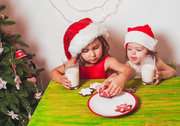 Deux petits pères noël boivent du lait et mangent des pains d'épice colorés