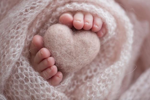 Deux petits pieds mignons de bébé enveloppés dans une couverture tricotée rose. et un coeur tricoté en fils de laine. photo de haute qualité