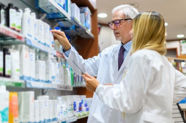 Deux pharmaciens, homme et femme, à la recherche d'un produit sur une étagère