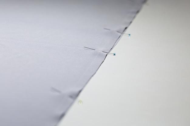 Deux pièces de tissu fixées par des aiguilles. industrie de la confection.