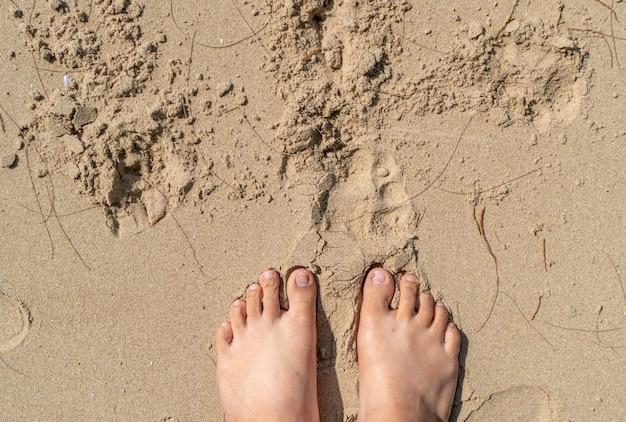 Deux pieds sur le sable de la plage, le temps des vacances.