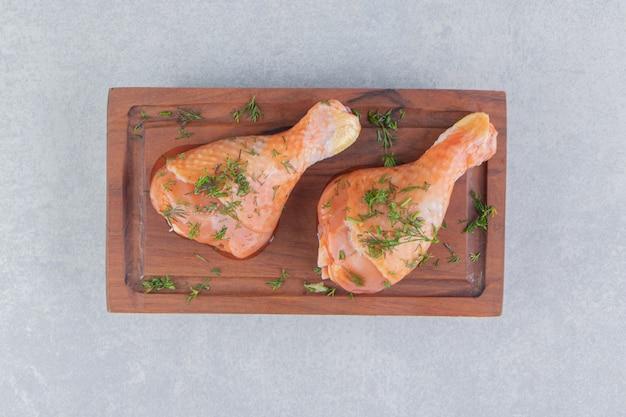 Deux pilons de poulet et tranches de citron, sur la surface bleue