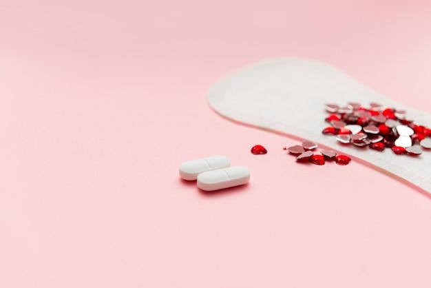 Deux pilules et tampon de menstruation avec un cœur rouge dessus, concept de contraception anti-douleur