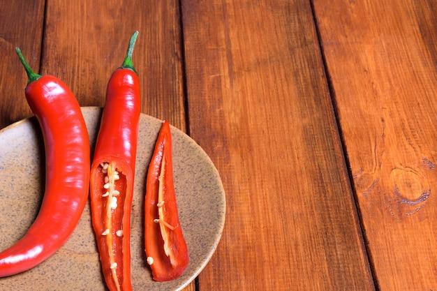 Deux piments rouges frais se trouvent sur une soucoupe brune sur une table en bois brune sur le côté gauche.