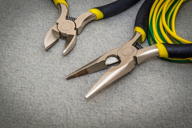 Deux pinces et des fils pour un électricien sur fond gris sont utilisés par le maître pour réparer l'électricité