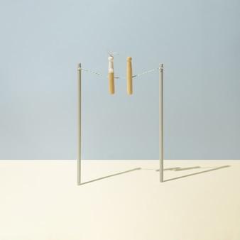 Deux pinces à linge, une en forme de lapin, se fixent sur une corde à linge sur fond bleu pastel et jaune. concept minimaliste. disposition carrée