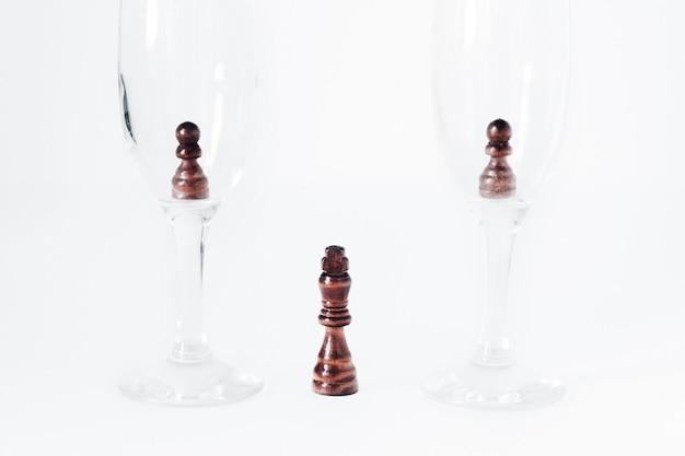 Deux pions dans deux verres. au fond, entre les verres, se tient le roi.