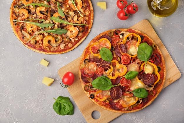 Deux pizzas à la mozzarella, au salami et aux fruits de mer