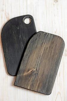 Deux planche à découper noire sur une table en bois blanche. copiez l'espace.