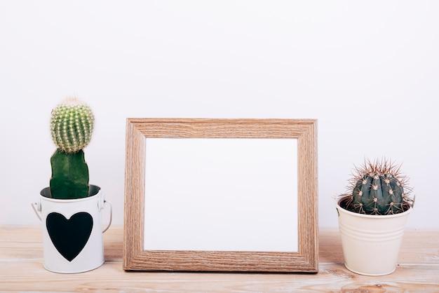 Deux plantes succulentes sur les côtés du cadre photo vide sur un bureau en bois