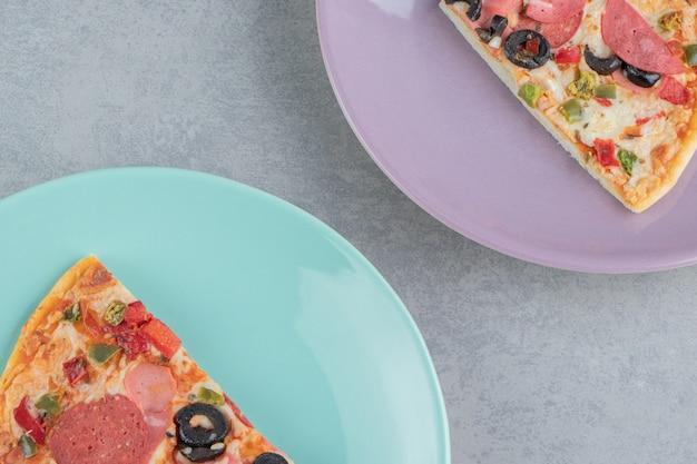 Deux plateaux avec des tranches de pizza sur marbre