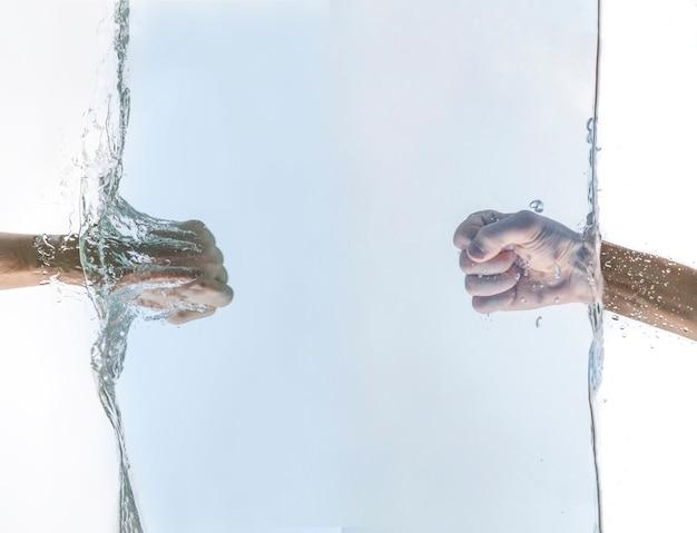 Les deux poings d'amis se frappent sous l'eau, traversent la surface de l'eau, concept de relation de réussite