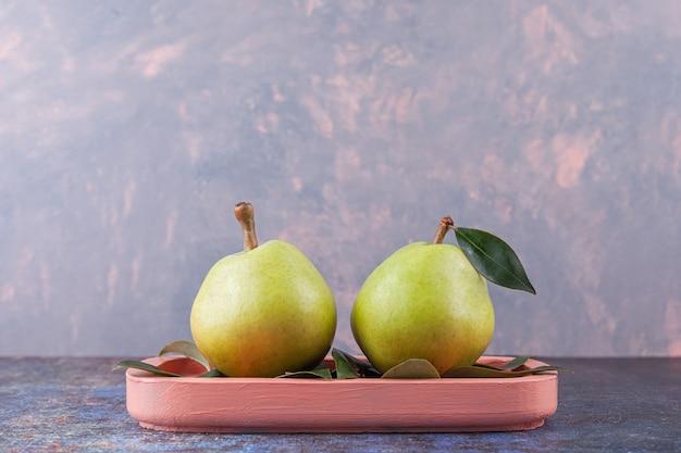 Deux poires vertes mûres avec des feuilles placées sur une planche en bois rose.