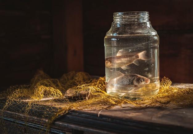 Deux poissons carpes dans un bocal en verre sur la table avec un filet de pêche. pêche nature morte.