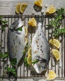 Deux poissons dorado avec des herbes et du citron sur le gril pour la cuisson