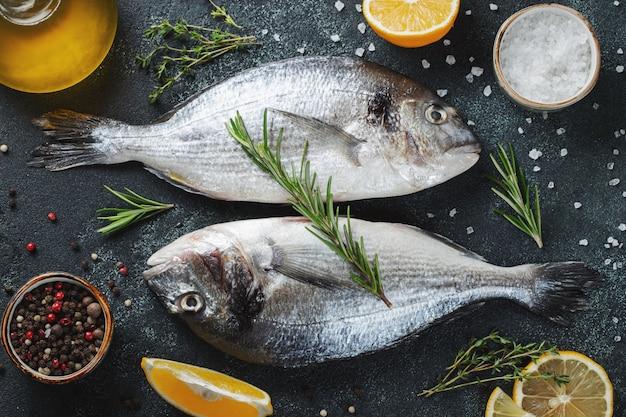 Deux poissons frais dorado crus aux épices et à l'huile d'olive