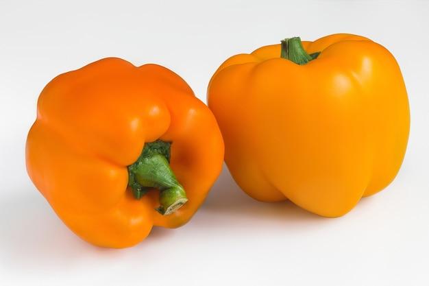 Deux poivrons orange mûrs sur fond blanc isolé