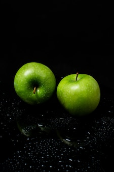 Deux pomme verte sur fond noir