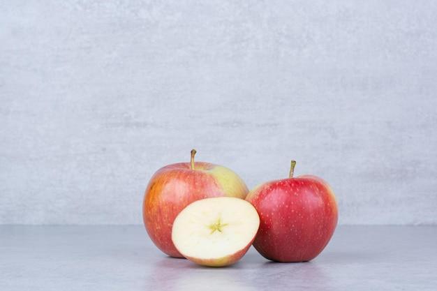 Deux pommes entières avec des tranches sur blanc