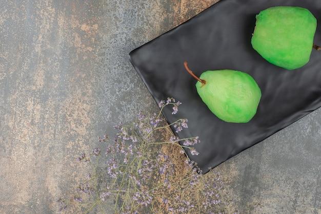Deux pommes fraîches pelées sur une plaque sombre sur une surface en marbre.