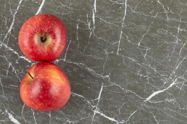 Deux pommes fraîches sur pierre grise.