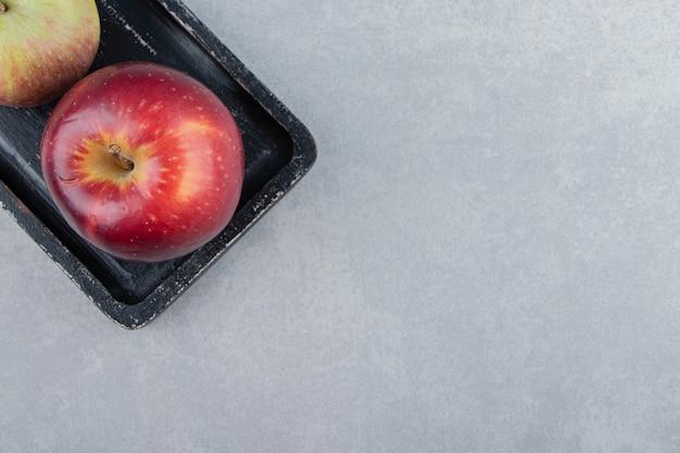 Deux pommes fraîches sur une planche à découper noire.