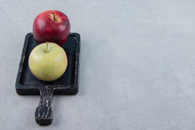 Deux pommes fraîches sur une planche à découper noire
