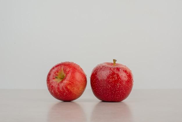 Deux pommes fraîches et rouges sur fond blanc.