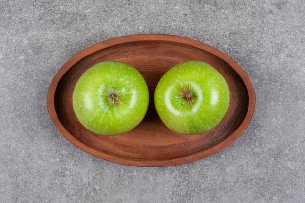Deux pommes fraîches vertes sur planche de cuisine en bois
