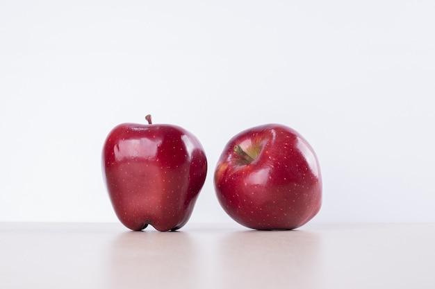 Deux pommes rouges sur blanc.