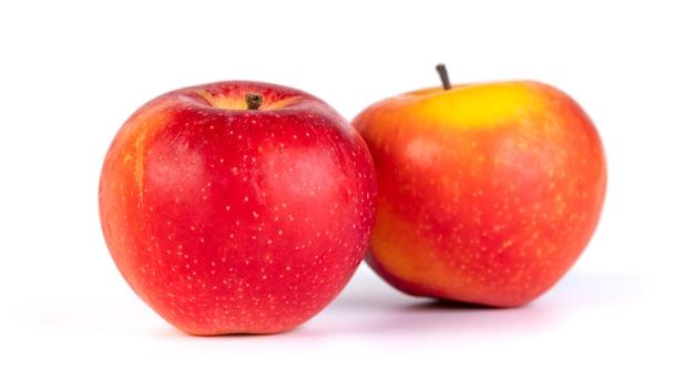 Deux pommes rouges fraîches isolées sur des aliments sains et blancs
