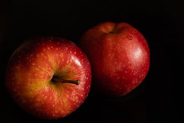 Deux pommes rouges fraîches mûres avec des gouttes d'eau sur une peau brillante sur fond noir