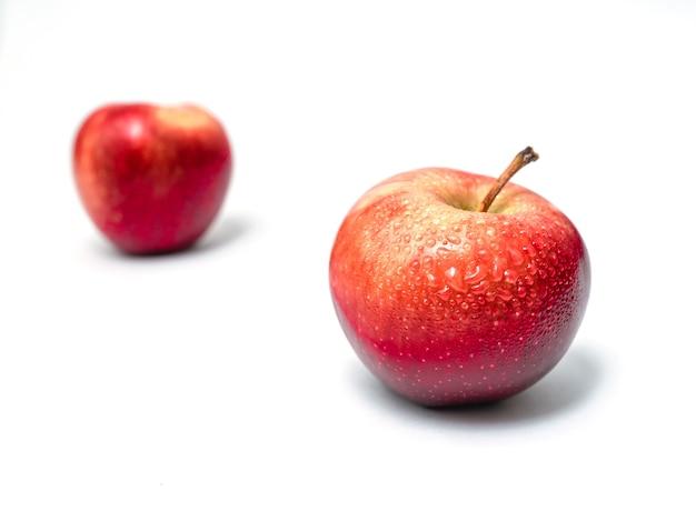 Deux pommes rouges isolées. délicieux dessert sucré. vue de côté. avec des gouttes d'eau.