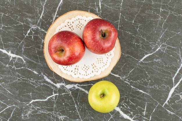 Deux pommes rouges et une verte. sur planche de bois.