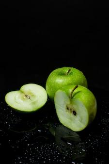 Deux pommes vertes coupées en deux sur un fond noir