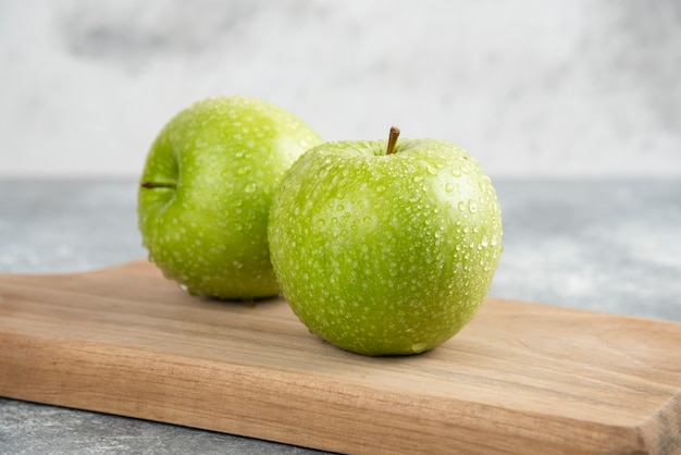 Deux pommes vertes entières sur une plaque en bois sur une table en marbre.