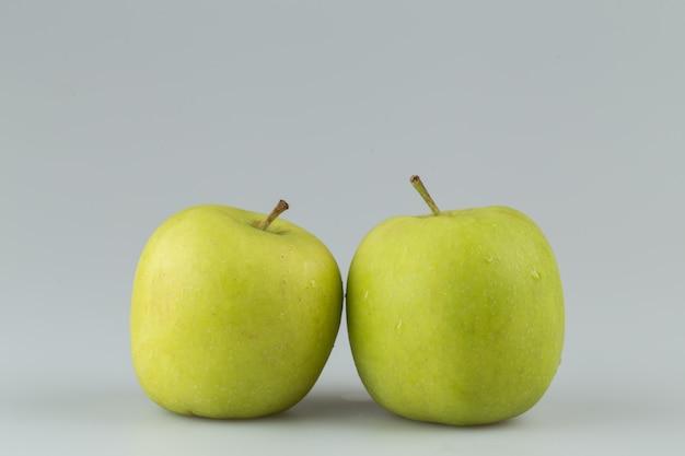 Deux pommes vertes isolées en surface grise