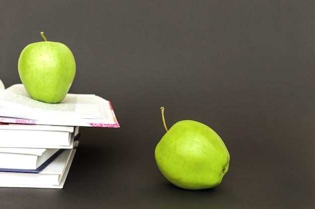 Deux pommes vertes et livres ouverts