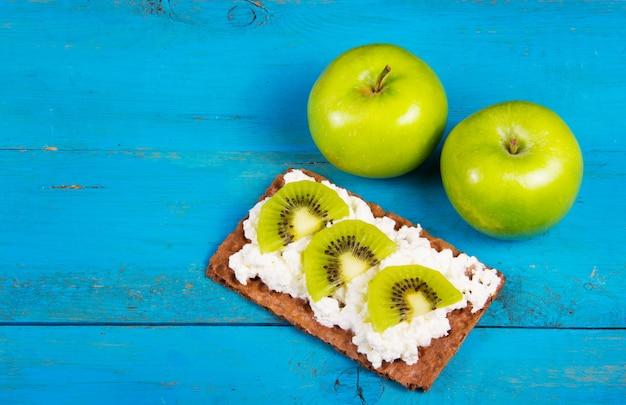 Deux pommes vertes et sandwich aux grains sains avec du fromage à la crème et des tranches de kiwi. un petit-déjeuner maison utile. la nourriture végétarienne. nourriture saine et savoureuse. copiez l'espace.