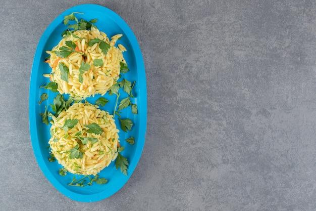 Deux portions de délicieux riz sur plaque bleue. photo de haute qualité