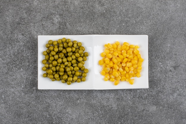 Deux portions de légumes en conserve. pois verts et graines de maïs sucré sur plaque blanche