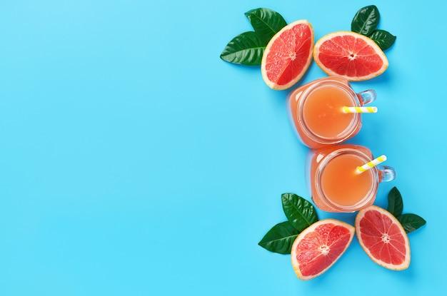 Deux pot de jus de pamplemousse frais sur un fond bleu. vue de dessus