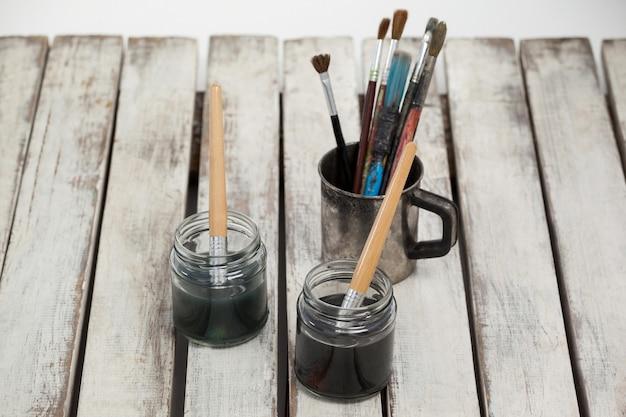 Deux pots d'aquarelle et pinceaux sur table en bois