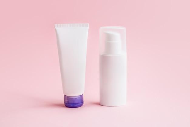 Deux pots de maquette de crème pour le visage pour la conception isolée sur fond rose. pot avec flacons de soins de la peau pour gel, lotion, crème.