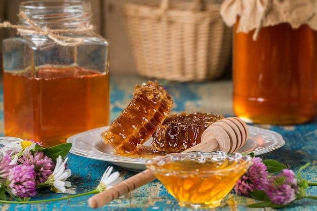 Deux pots de miel avec nid d'abeille sur une table en bois avec des fleurs