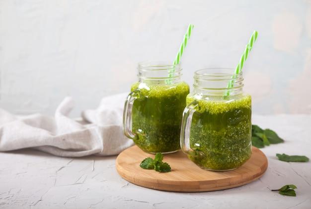 Deux pots avec des smoothies verts sur un support en bois sur un fond gris béton. alimentation équilibrée. détox.