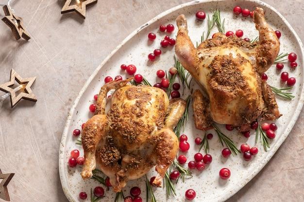 Deux poulets entiers rôtis aux canneberges et tranches d'orange.