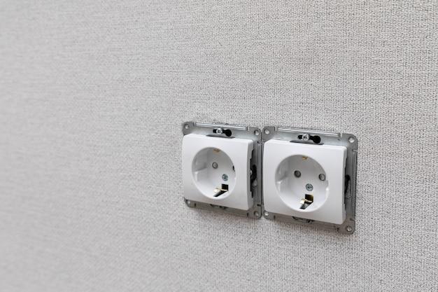 Deux prises électriques européennes de type f sans cadre décoratif en plastique installées au mur